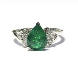 Emerald and diamond cluster ring, the pear shape emerald weighing 1.39 carats in a three claw setting with round brilliant cut diamonds to each shoulder, mounted in 18ct white gold.