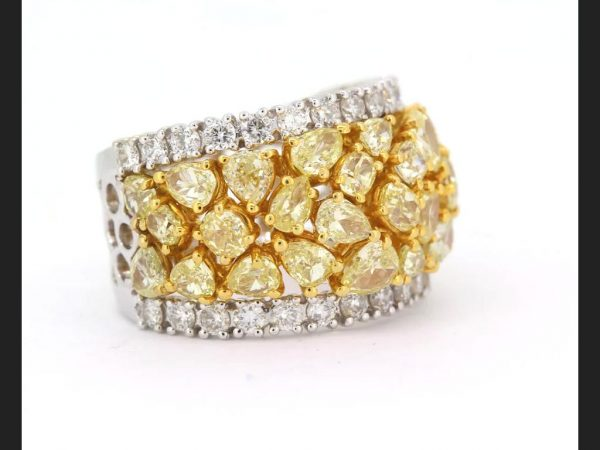 Yellow and White Diamond Ring; Central band of pear, round and oval cut fancy yellow diamonds, highlighted by round cut white diamonds, est. total 3.50 ct