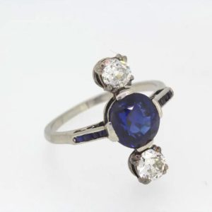 Art Deco Natural Sapphire and Diamond Ring; Central round cut natural sapphire flanked by two round cut diamonds, square cut sapphire shoulders, c.1920
