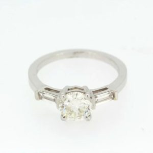 Solitaire Diamond Ring; central 1.23ct round cut diamond, flanked by baguette shoulders totaling 0.33ct, detailed 750, 18ct white gold
