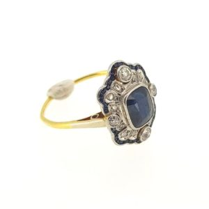 Vintage Sapphire and Diamond Ring in the Art Deco style; Central cushion cut sapphire encompassed by round cut diamonds and baguette cut sapphires.