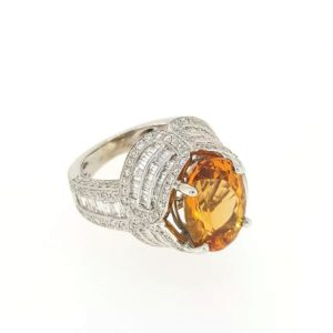 Brazilian Topaz and Diamond Dress Ring; Oval cut Brazilian topaz in four claw setting, surrounded by an intricate design of round and baguette cut diamonds