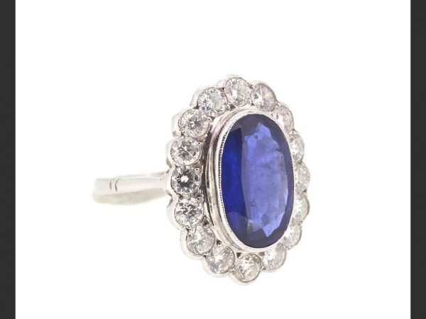Vintage Sapphire and Diamond Cluster Ring; Central oval cut sapphire surrounded by round cut diamonds, 18ct white gold (Sapphire 4.11ct, diamonds 1.55ct)