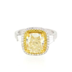 4.02 carat central cushion cut yellow diamond within a double halo of yellow and white round cut diamonds, with baguette shoulders.