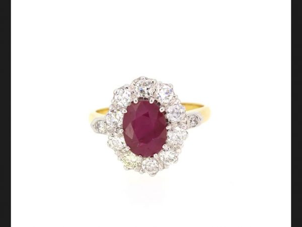 Ruby and Diamond Cluster Ring; Central oval cut 2.20 carat ruby surrounded with a total of 1.25 carats brilliant cut diamonds. Detailed 18ct yellow gold