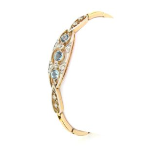 Edwardian Aquamarine and Diamond Panel Bracelet; Three round cut aquamarines accentuated by round cut diamonds, expanding strap, c.1910, 15ct gold
