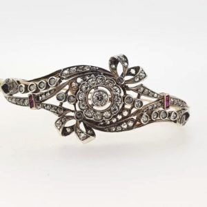 Vintage bangle set with round cut diamonds displaying an intricate floral bow design, finished with two princess cut rubies on either side. Circa 1930's