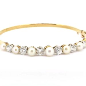 An elegant example of an Edwardian hinged bangle set with natural pearls and diamonds, in 18ct yellow gold a platinum. A beautiful and timeless piece