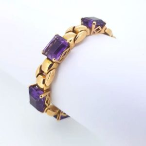 Amethyst bracelet; Five emerald cut amethysts in four claw settings, dispersed throughout a solid knot design 18ct yellow gold bracelet, circa 1940's