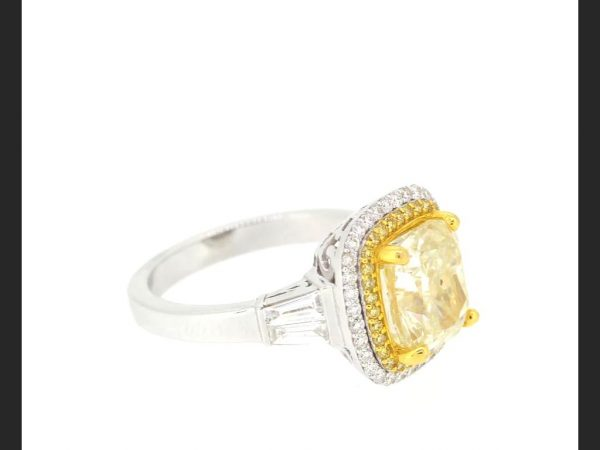 Fancy Yellow Diamond Cluster Ring; 4.02 carat central cushion cut yellow diamond within a double halo of yellow and white round cut diamonds, baguette shoulders.