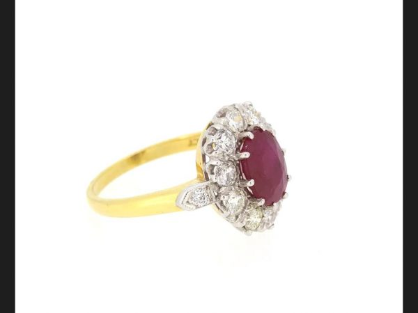 Ruby and Diamond Cluster Ring; Central oval cut 2.20 carat ruby surrounded with brilliant cut diamonds. Detailed 18ct yellow gold