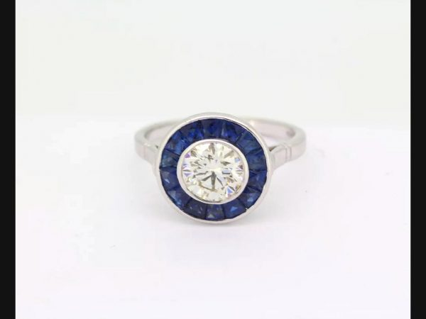 Vintage Art Deco Style Sapphire and Diamond Calibre Set Ring; round cut 1.21ct diamond encircled by sapphires.