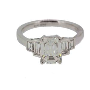 emerald cut diamond engagement ring weighing 1.83 carats flanked by two baguette cut diamonds to each side. Mounted in platinum.
