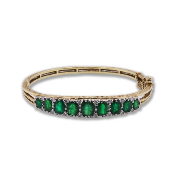 Vintage Emerald and Diamond Bangle; ornately carved hinged bangle, set with nine graduated emeralds, 9.00cts, diamond surround, 9ct yellow gold, with safety chain and clasp