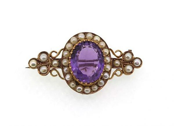 Antique Victorian Amethyst and Pearl Cluster Brooch; A pretty brooch set with an oval-faceted amethyst and split pearls. Mounted in high carat gold.