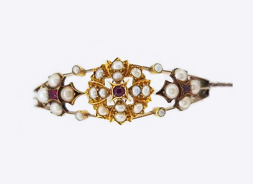 Antique Edwardian Pearl and Ruby Bangle; A delicate Edwardian bangle set with pearl clusters featuring central rubies. Marked for 15ct yellow gold.