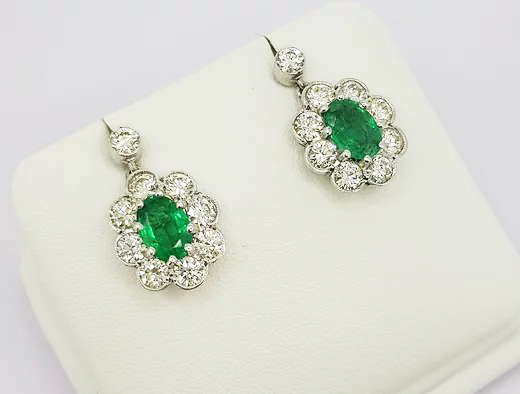 Emerald and Diamond Cluster Drop Earrings; 1.40 carat oval emeralds, surrounded by 1.75cts brilliant-cut diamonds, diamond stud to post, in 18ct white gold