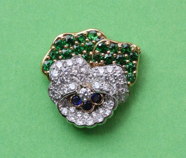 Vintage Tiffany and Co Diamond, Tsavorite Garnet and Sapphire Pansy Flower Brooch; set with 1.10ct tsavorite garnets and 2.10cts brilliant diamonds, Signed