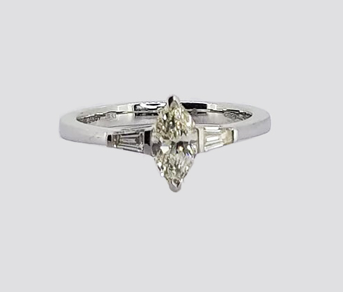 0.57ct Marquise Cut Diamond Engagement Ring; 0.57 carat marquise-cut diamond flanked by 0.21cts tapered baguette-cut diamonds, in 18ct white gold