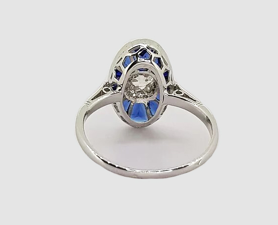 Art Deco style Sapphire and Old Cut Diamond Oval Cluster Ring; central old-cut diamond surrounded by calibre-cut sapphires, mounted in 18ct white gold.