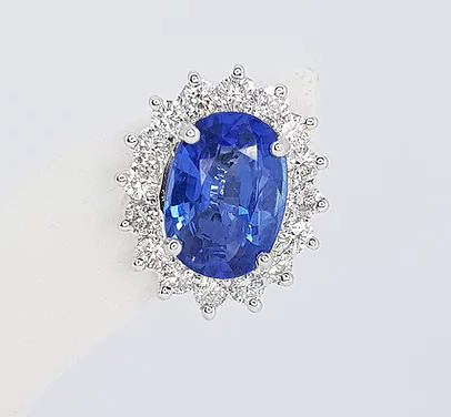 Sapphire and Diamond Oval Cluster Earrings; 2.46cts oval faceted sapphire surrounded by 0.78cts brilliant-cut diamonds, in 18ct white gold.