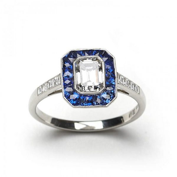Emerald Cut Diamond and Sapphire Cluster Ring; 0.69ct E VS2 emerald-cut diamond surrounded by calibre-cut sapphires, square-cut diamond set shoulders, mounted in platinum