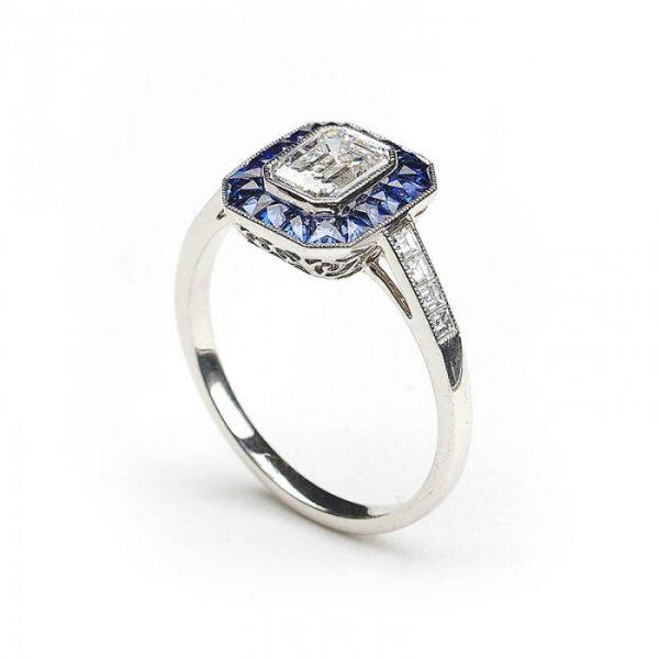 0.69ct Emerald Cut Diamond and Sapphire Cluster Ring, E VS2, Square-cut diamond set shoulders, mounted in platinum