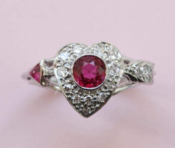 Vintage 1950s Ruby and Diamond Heart and Arrow Ring; 0.75ct round old-cut ruby surrounded by 0.30cts diamonds, in platinum and white gold