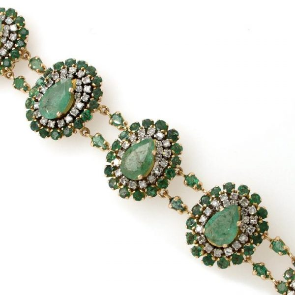 Vintage Emerald, Diamond and Gold Cluster Bracelet; featuring seven articulated clusters with central pear-shaped emeralds within diamond and emerald surrounds, Circa 1970s