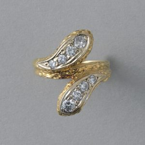 Vintage Diamond and 18ct Yellow Gold Snake Ring; two snake heads set with graduating brilliant diamonds, scaly structure to shank, France, Circa 1970. Attributed to Van Cleef & Arpels