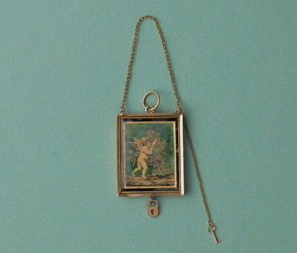 Early 19th Century 18ct Gold Angel Locket; black and gold 'verre eglomisé' angel picking roses, miniature key and lock, French gold mark for 1809-1819