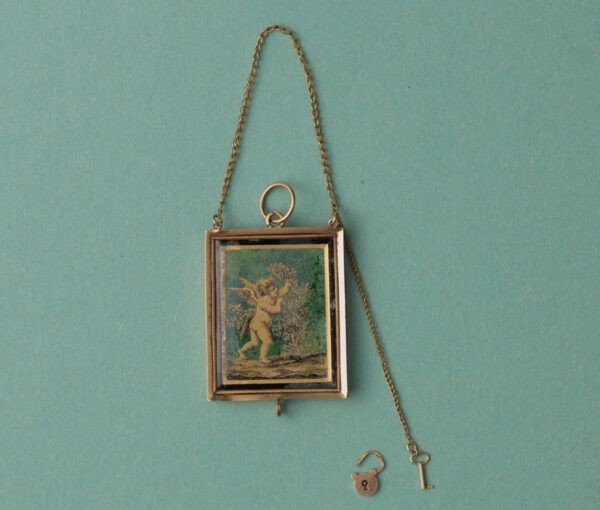 Early 19th Century 18ct Gold Angel Locket; black and gold gilded angel picking roses, miniature key and lock, French gold mark for 1809-1819