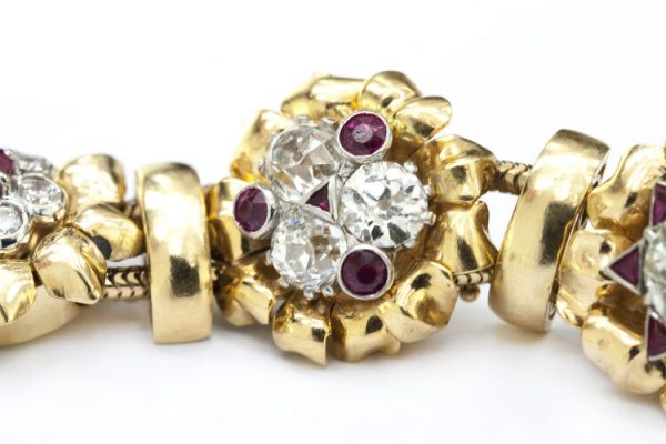 Vintage 7ct Diamond and Ruby Cluster Bracelet; set with 7.00 carats of diamonds and 3.00 carats of rubies in intricate and unique floral clusters surrounded by gold leaves, in 18ct yellow gold, Circa 1930s