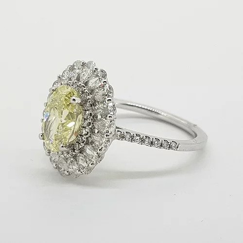 Fancy Yellow Diamond Cluster Ring with GIA Certificate; 1.59ct Oval Fancy Yellow GIA certified Natural Diamond surrounded by 0.15cts brilliant white diamonds and an outer border of 0.90cts pear-shaped diamonds, giving a scalloped edge finish, mounted in platinum