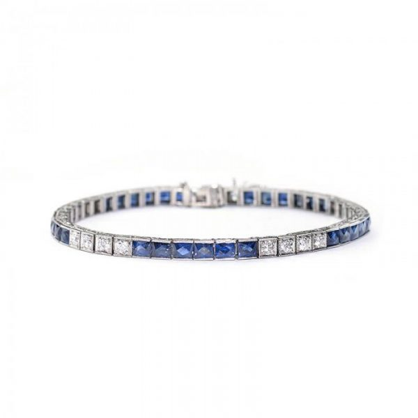 Antique Art Deco Sapphire and Diamond Line Bracelet; alternating pattern of six French-cut sapphires in channel settings and four round brilliant-cut diamonds in box settings. Crafted from platinum, all settings are individually hinged with millegrain edges. The sides are engraved with a millegrain and foliate design. Circa 1935