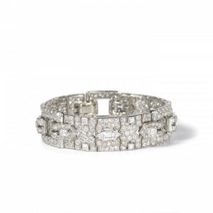 Vintage Cartier Diamond Bracelet; comprised of three panels, each set with a central trap-cut diamond flanked by triangular and fancy-cut diamonds, accented with transitional brilliant-cut and single-cut diamond set surrounds, 18.70 carat total. Mounted in platinum. Circa 1930