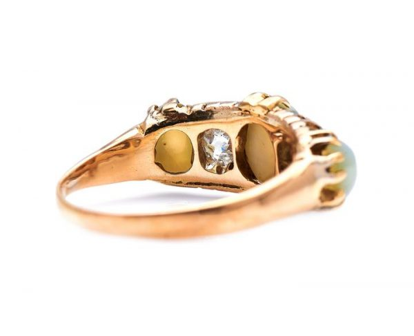 Antique Victorian Cats Eye Chrysoberyl and Diamond Five Stone Ring; set with a trio alluring chrysoberyl stones spaced by a pair of charming antique cushion-shaped diamonds, claw-set in 18ct yellow gold