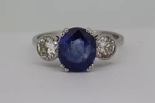 Sapphire and Diamond Three Stone Ring; central 2.90ct oval faceted sapphire, double four-claw set, flanked by 1.30cts brilliant cut diamonds in a rubover setting with millegrain edges, in 18ct white gold