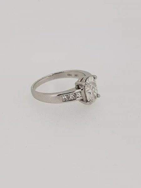 Oval Cut Diamond Engagement Ring with Princess Cut Shoulders; central 1.22 carat oval-cut diamond in a four-claw setting, with 0.36cts princess-cut diamond set shoulders, in 18ct white gold