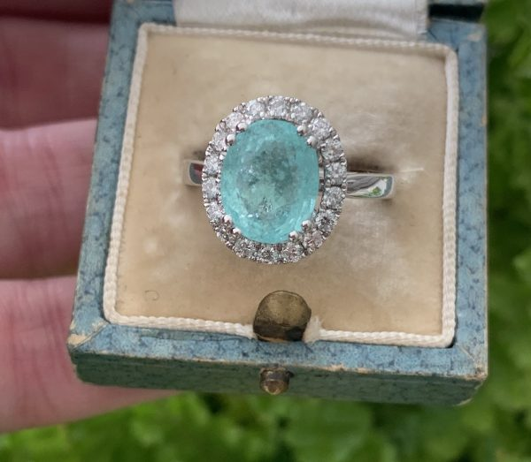 Paribia Tourmaline and Diamond Cluster Ring in 18ct White Gold; 3.73 carat oval faceted aqua/greenish-blue Paribia tourmaline surrounded by diamonds