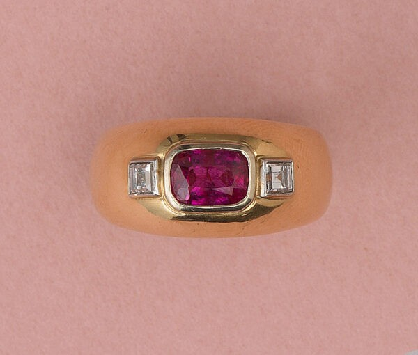Vintage French Ruby and Diamond Three Stone Dress Ring in 18ct Yellow Gold; 1.68ct table cut unheated ruby flanked by carré cut diamonds, Circa 1950s-1970s