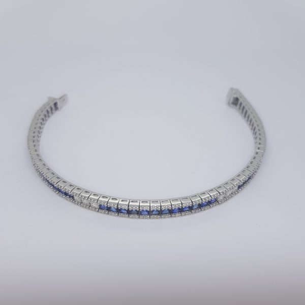 Princess Cut Sapphire and Diamond Line Bracelet; central line of alternating sections of square cut sapphires and diamonds, flanked by rows of brilliant-cut diamonds, in 18ct white gold. Sapphires 7.03 carats. Diamonds 2.21 carats