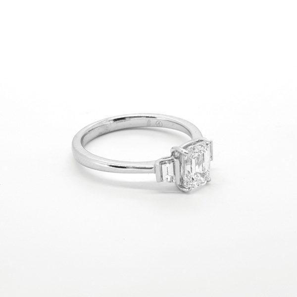 1ct Emerald Cut Diamond Ring with Baguette Shoulders; central claw set emerald-cut diamond accented with a channel-set baguette-cut diamond to each shoulder, in 18ct white gold