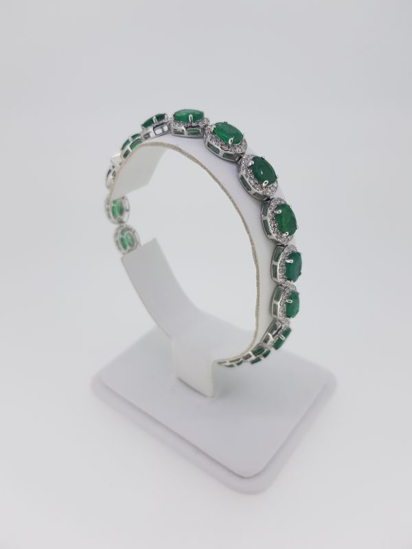 Emerald and Diamond Cluster Bracelet; each cluster features an oval faceted emerald with a diamond surround, in 18ct white gold. Emeralds 13.00 carats. Diamonds 3.20 carats