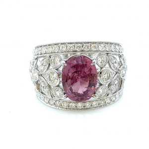 3.19ct Padparadscha Sapphire and Diamond Dress Ring by David Jerome; the central, unheated 3.19 carat oval faceted padparadscha sapphire is nestled upon a wide floral openwork band set with 1.56 carats of sparkling white diamonds, in 18ct white gold