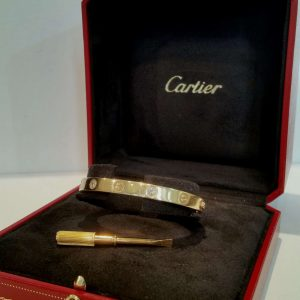 Cartier Love Bangle with Diamonds; 18ct yellow gold Cartier love bangle set with four brilliant-cut diamonds. Size 17. Comes with box, screwdriver and current valuation from Cartier
