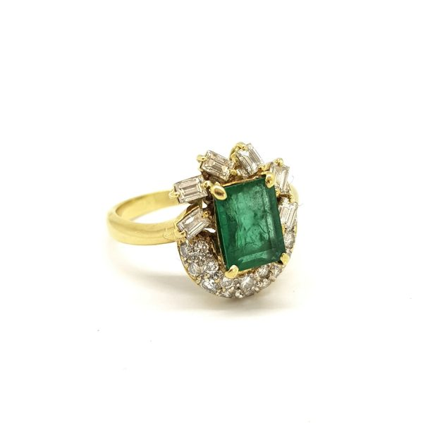 Vintage Emerald and Diamond Cluster Dress Ring; 2ct emerald-cut emerald surrounded by 1.20cts baguette and brilliant cut diamonds, in 18ct yellow gold