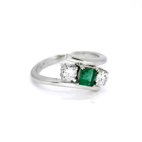Emerald and Diamond Crossover Three Stone Ring; central princess-cut emerald flanked by brilliant-cut diamonds, in 18ct white gold with stylish crossover design