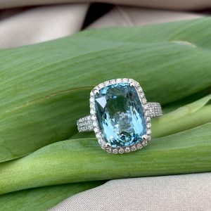 Aquamarine and Diamond Dress Ring; 6.21ct cushion-shaped oval faceted aquamarine with diamond surround and three rows of diamonds to each shoulder, in 18ct white gold with pierced heart detail to under-gallery