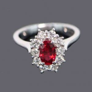 Burmese Ruby and Diamond Cluster Ring; 1.01ct oval faceted Burma ruby surrounded by 0.65cts diamonds, 18ct white gold. No indication of heat treatment